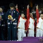 Second placed athletes of Japan react as China's athletes celebrate gold after the men's gymnastics team final in the North Greenwich Arena during the London 2012 Olympic Games