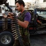 A member of the Free Syrian Army carries ammunition as he prepares for their patrol in Attarib, on the outskirts of Aleppo province