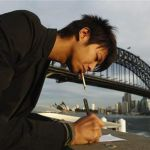 An office worker smokes a cigarette as he takes notes in front of the Sydney Harbour Bridge
