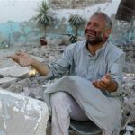 A man cries in front of houses destroyed during a recent Syrian Air Force air strike in Azaz