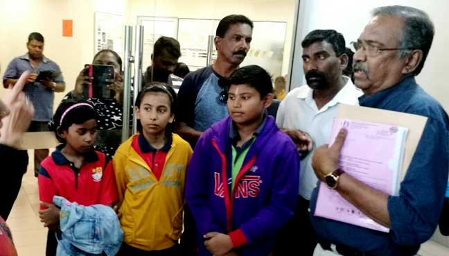 Freedom NGO chief N Ganesan (right) speaking with an officer from the Penang Education Departmemt, with Vengadesan's family on tow.