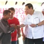 chief minister Lim Guan Eng (second left) giving a Kampung Permatang Tok Suboh villager his offer letter.
