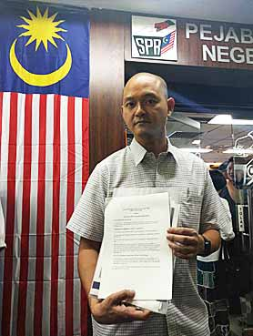 Serdang-MP-Ong-Kian-Ming,-holding-the-EC-rules-and-regulations.