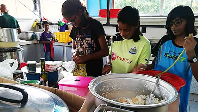 Children at the Lighthouse shelter helping workers cook food provided by The Lost Food Project.