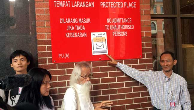 (From right) Teoh Beng Hock Trust for Democracy foundation secretary Faisal Mustaffa, president A Samad Said, Beng Hock's sister Lee Lan and executive secretary Ng Yap Hwa after pasting the invitation letter on MACC's wall. They had refused to enter MACC building when they were ordered to surrender their phones.