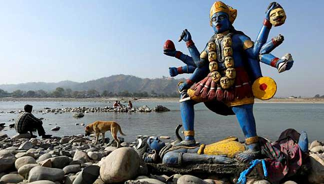 A man sits next to a damaged idol of Hindu goddess Kali which was taken out after its immersion in the river Ganges in Haridwar.
