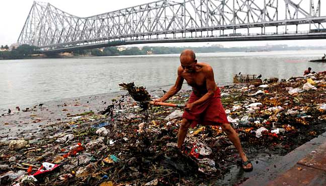 A man cleans garbage along the banks of the river Ganges in Kolkata.
