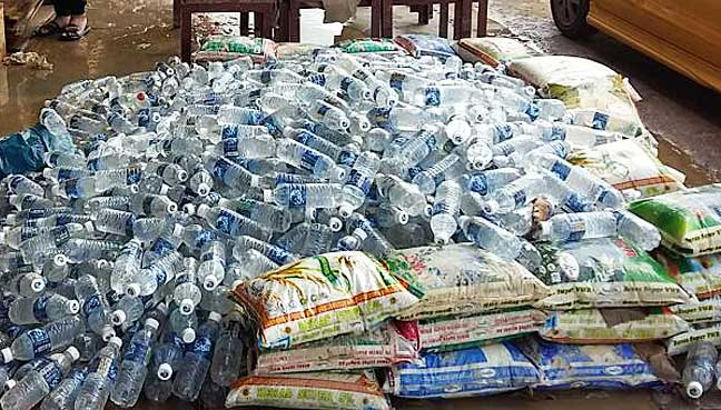 Hundreds of bottles of drinking water and sacks of rice damaged by flood in Kinarut town.