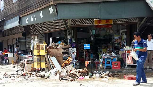 Damaged groceries taken out to the sidewalk after the flood the night before in historic Kinarut town.
