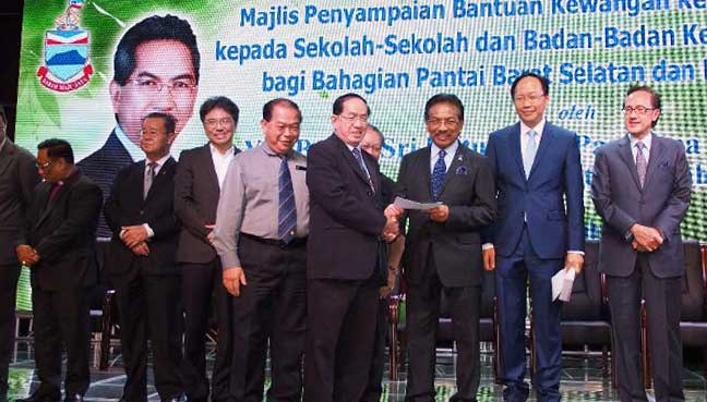 Sabah Dong Zong chairman Jimmy Yong receiving a grant from chief minister Musa Aman.