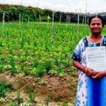 60-year-old Muniamah Kutusamy standing in front of her late husband's farm while holding the land grant she was awarded.
