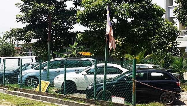 A tattered Jalur Gemilang inside a used car lot at Jalan Perkasa just before the Jalan Pria junction in Kuala Lumpur.