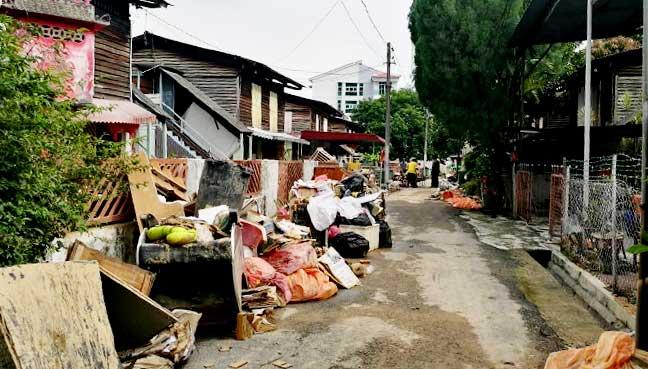 Heaps of damaged goods line the roadside along the main road in Kg Shaik Madar, Air Hitam, Penang.