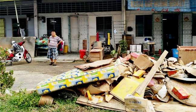 Tau sar pneah biscuit maker Tan Chor Huat looking at the heap of damaged goods from his shop in Kg Shaik Madar, Air Hitam.