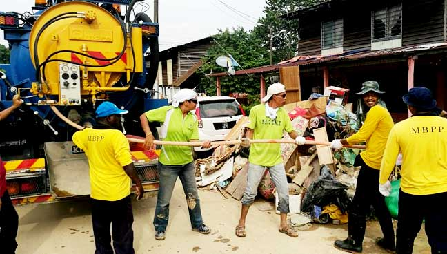 Penang Island City Council (MBPP) workers clearing out a drain at Kg Shaik Madar. The council's limited assets such as backhoes and lorrys have impeded the speed of the clear up.