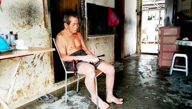 Tho Yuo Seng, 76. The half blind man claims to have been nearly floated away by the gushing floodwaters over the weekend.