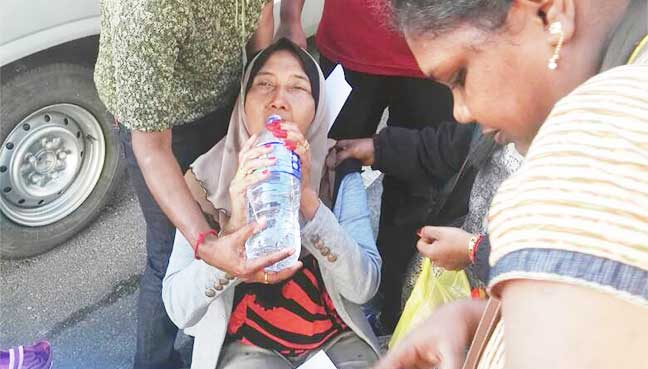 Sharifah Hanim, 52, being given water by other Cameron Highlands residents after she fainted outside the police station.