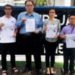 Chris Lee (2nd left) outside the North East district police headquarters in George Town after lodging his report against the Besut Umno Youth chief.
