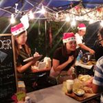 Hawkers wearing Christmas hats trying their best to attract customers.
