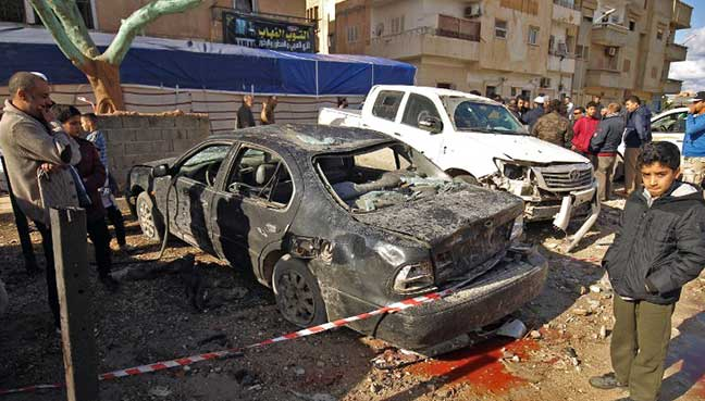 Libyans check the aftermath of an explosion in the eastern city of Benghazi. The bombers struck after evening prayers on Tuesday, blowing up two cars 30 minutes apart outside the mosque in Al-Sleimani.