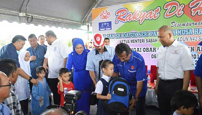 Musa hands over a school bag to a schoolgirl. Courtesy of TNB in Sandakan.