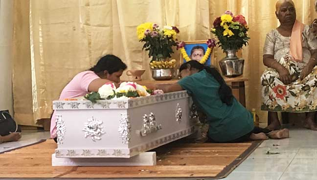 M. Vasanthapiriya's sister (right) and her cousin are hunched over the casket bearing the body of their loved one, at their family home in Kampung Tong Hai, Nibong Tebal, today.
