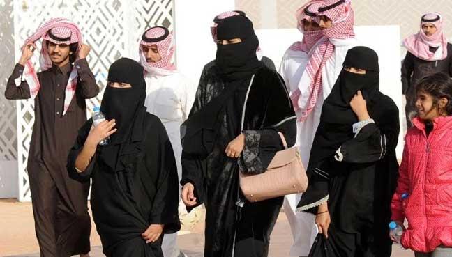 A picture taken on Jan 19, 2018 shows Saudi women and men walking during the King Abdulaziz Camel Festival in Rumah.