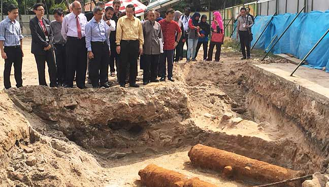 Penang Chief Minister Lim Guan Eng (in yellow shirt), flanked by his deputy Mohd Rashid Hasnon (in blue), and chief archaeologist Prof Mohd Mokhtar Saidin (in dark-grey), together with the Fort Cornwallis conservation team at the site where the two cannons were discovered.