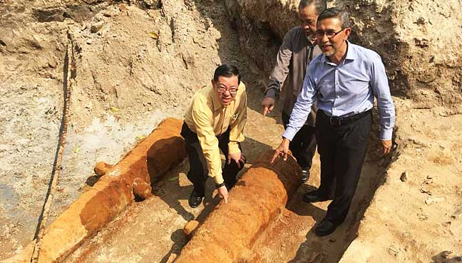 (From left) Penang Chief Minister Lim Guan Eng, chief archaeologist Prof Mohd Mokhtar Saidin and Deputy Chief Minister Mohd Rashid Hasnon pointing towards the 'GR' inscription on one of the cannons found at Fort Cornwallis.