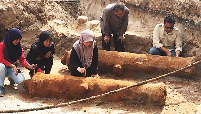 Chief archaeologist Prof Mohd Mokhtar Saidin (crouching) together with his team members checking on the two cannons discovered at Fort Cornwallis yesterday afternoon.