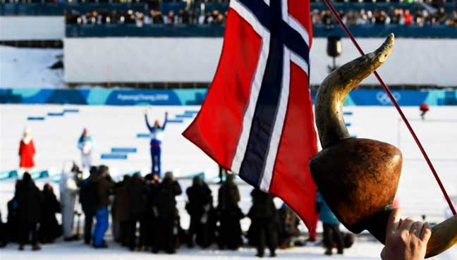 Norway's flag and a horned helmet are pictured as gold medallist Marit Bjoergen of Norway celebrates on the podium between silver medallist Krista Parmakoski of Finland and bronze medallist Stina Nilsson of Sweden in the distance. (Reuters pic)