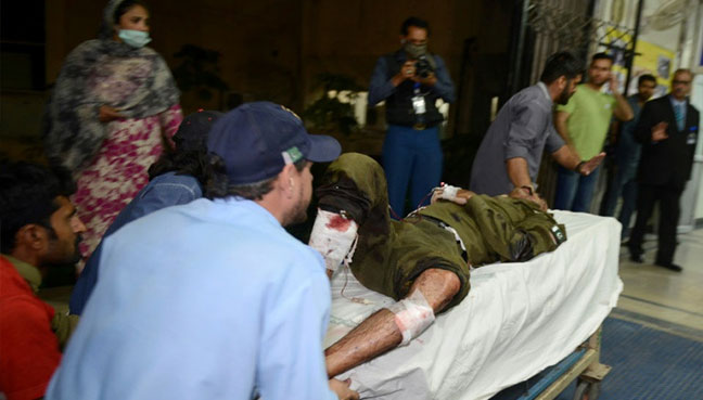 Pakistani rescue workers push a stretcher carrying an injured man to the hospital following the blast of a motorcycle bomb attack in Lahore