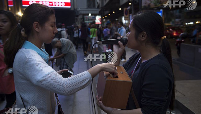 Woman donating money to a blind singer as she performs in front of a skytrain station in Bangkok.(AFP pic)