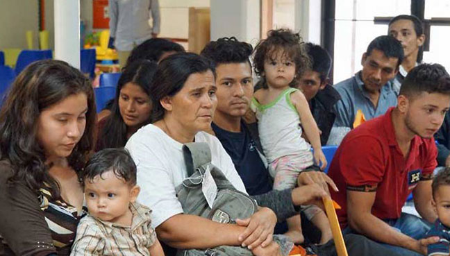 Migrants wait to be assisted by volunteers in a Humanitarian Respite Centre in the border town of McAllen Texas