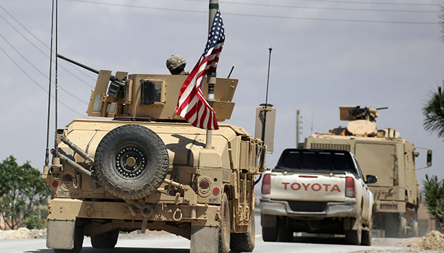 The US flag flutters on a military vehicle in Manbej countryside