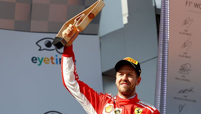 Ferrari's Sebastian Vettel celebrates with his trophy on the podium after finishing third