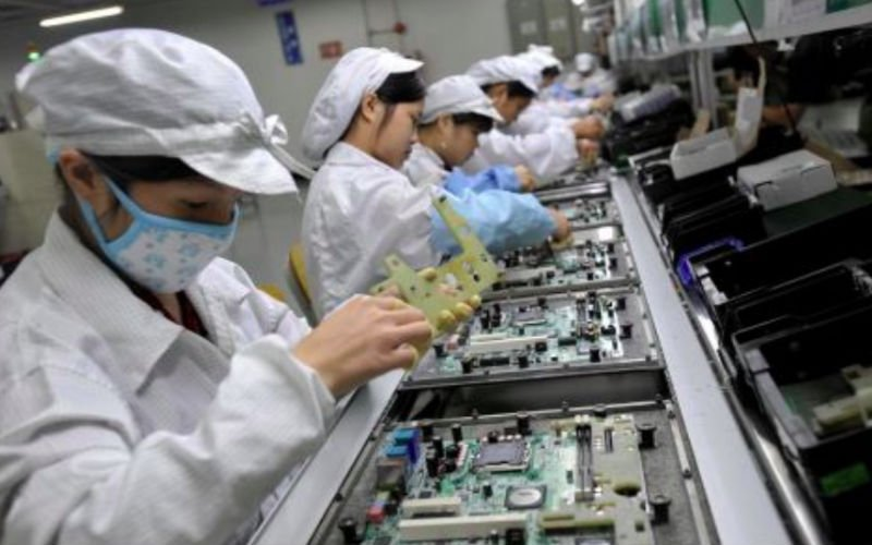Chinese workers assemble electronic components at the Taiwanese technology giant Foxconn's factory in Shenzhen China