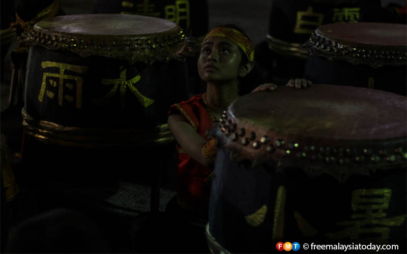 A young drummer sits in between the Tanggus, traditional drums played during lion dance performances.