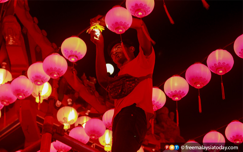 A man hangs lanterns at a temple in Kuala Lumpur. Red lanterns symbolise prosperity, and are used as decorations during major festivals.