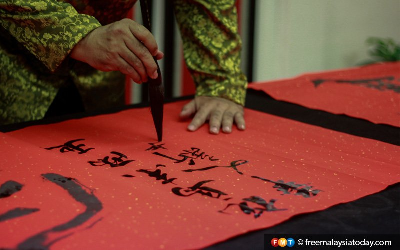 """Chinese calligraphy is a key feature of the Chinese New Year celebration. The word """"ong"""" (luck) is usually written on red paper in black ink using a special brush and hung around homes or business premises."""