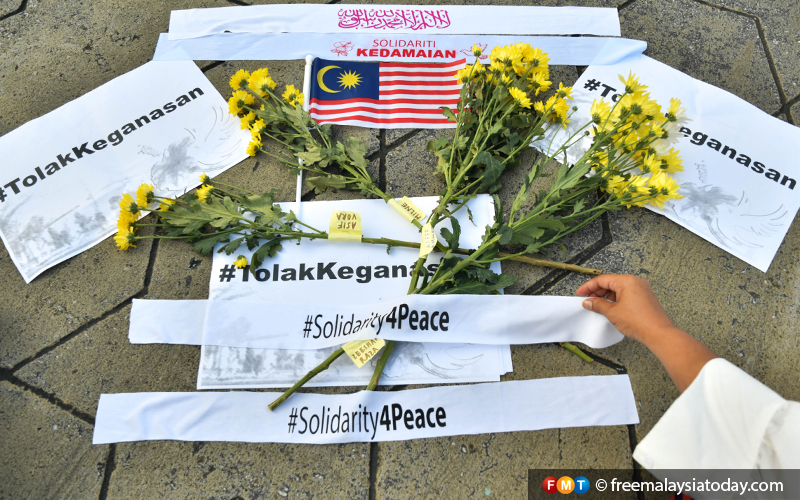 Slogans in support of peace laid on the ground together with flowers.
