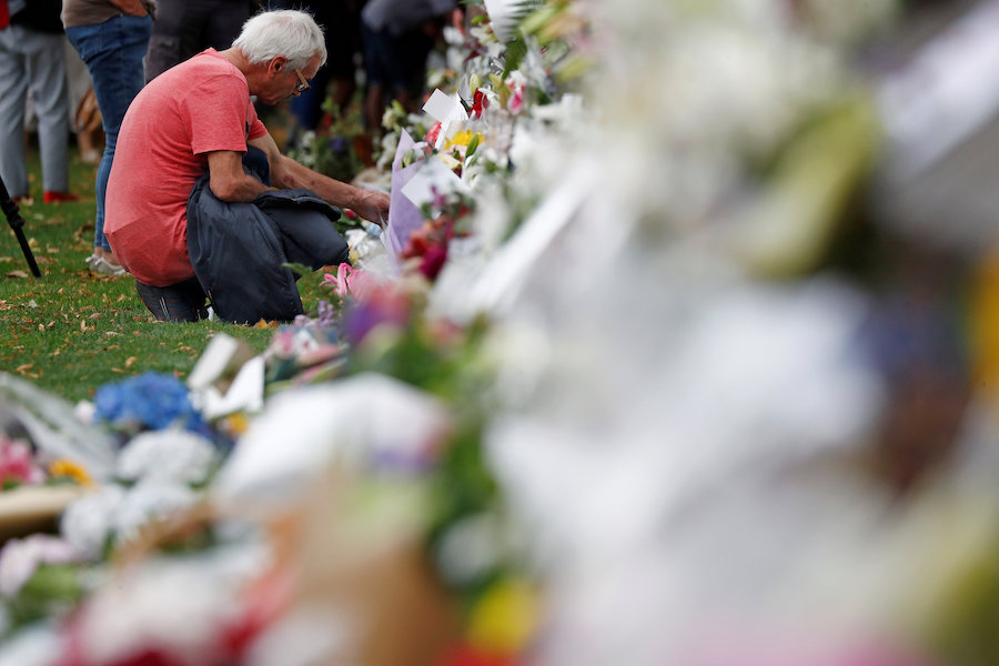 People place flowers at a memorial as a tribute to victims of the mosque attacks near Linwood mosque in Christchurch