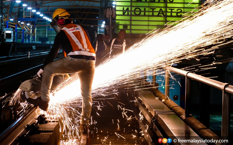 Sparks fly as a worker saws at the rail with a rail-cutting machine.
