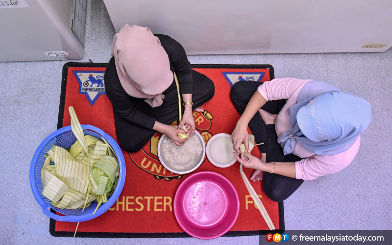 Nadira and an assistant spend hours sitting on the floor, wrapping the ketupat rice.