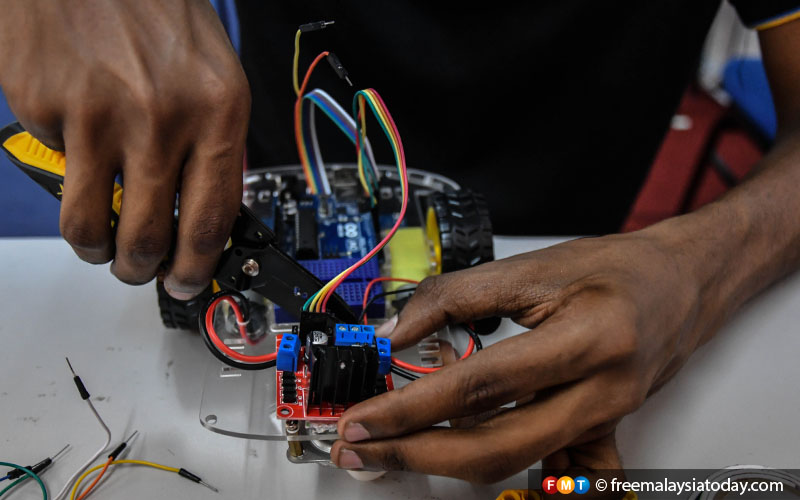 Laveneishyan connecting the battery snap to a motor controller which will allow the robot to follow a line on a grid. Line Following Robots are usually used to carry children at shopping malls, homes or entertainment centres, or for carrying parcels in industries. Laveneishyan is developing his robot for the RBTX Challenge 2019.