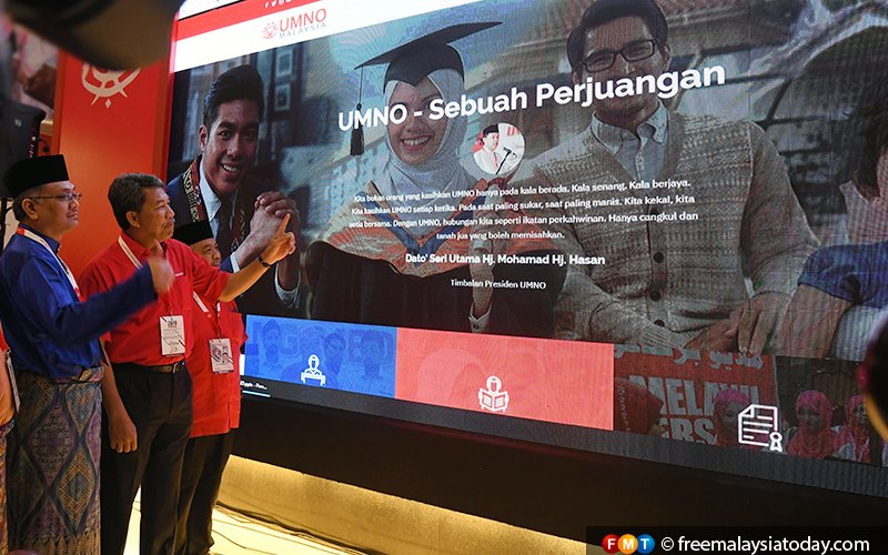 """Umno deputy president Mohamad Hasan (second left) looks at a screen showing the general assembly's theme, """"A Struggle"""", at the Putra World Trade Centre in Kuala Lumpur."""