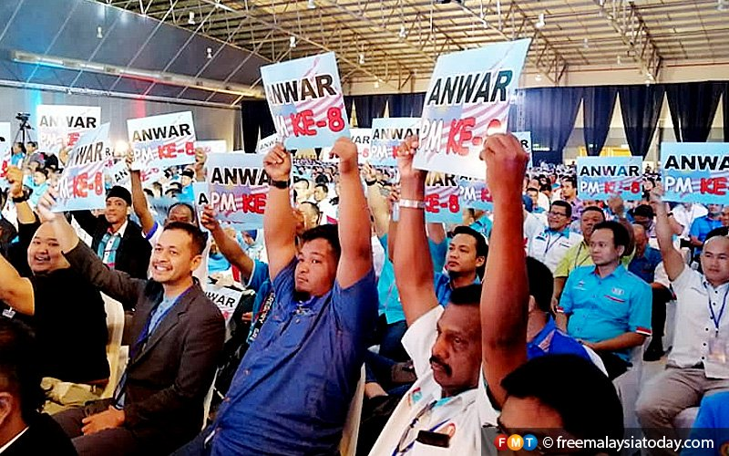 PKR members aligned with Anwar's faction carry placards in support of calls to fulfil Pakatan Harapan's promise to make the party president the eighth prime minister.