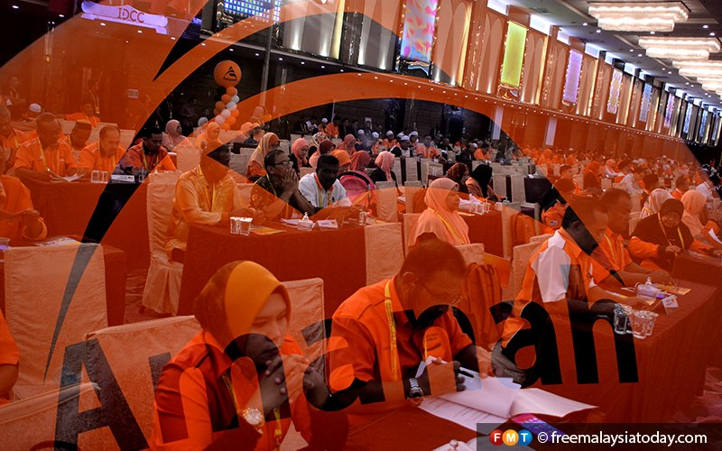 Delegates at the Amanah convention seen through the party's orange logo at the Ideal Convention Centre in Shah Alam.