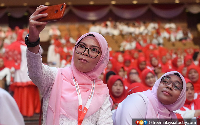 A Puteri Umno member takes a selfie as she joins thousands of others at the Putra World Trade Centre, Kuala Lumpur.