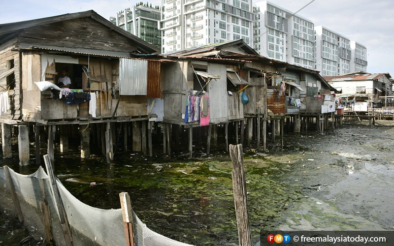 Makeshift houses on loose stilts in Kampung Sembulan Tengah are in stark contrast to the modern condominiums in the background.